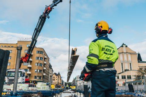Kisko on ilmassa ja sitä asetetaan paikalleen. Työntekijä ohjaa liikettä ohjaimella. Kuva Wille Nyyssönen.
